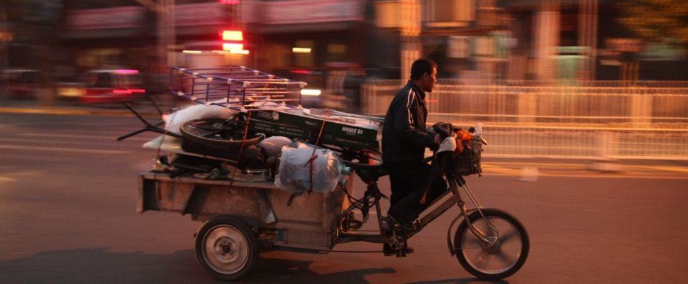 Hombre monta una motocicleta con plataforma de carga en China, sobre dts