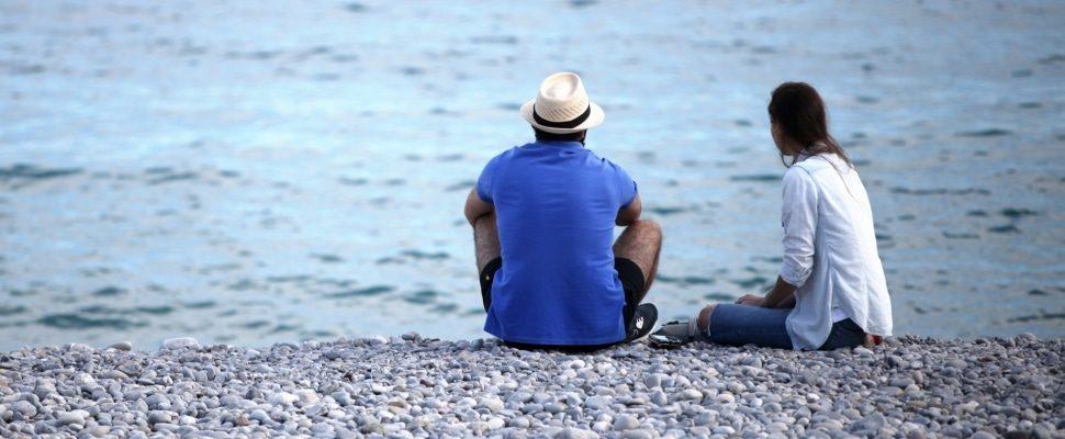 Hombre y mujer sentada en la playa, sobre dts
