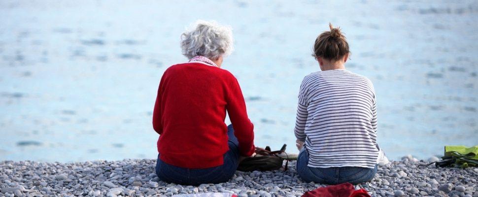 Alte und junge Frau sitzen am Strand, über dts